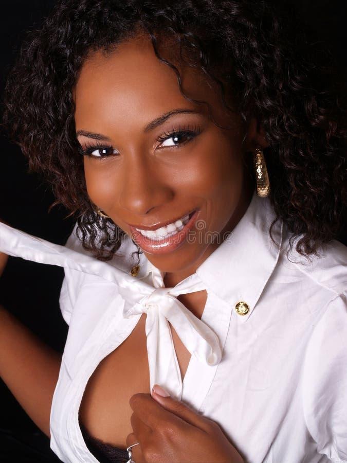 Donna di colore sorridente graziosa che inizia a undress fotografia stock