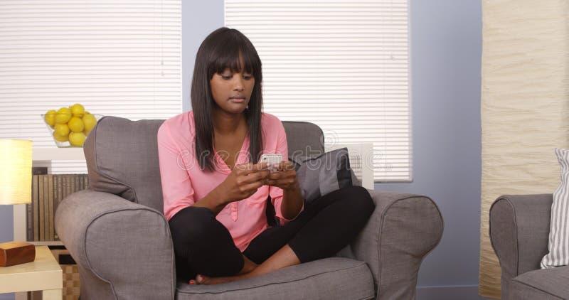 Donna di colore sveglia che per mezzo dello smartphone sullo strato fotografia stock libera da diritti