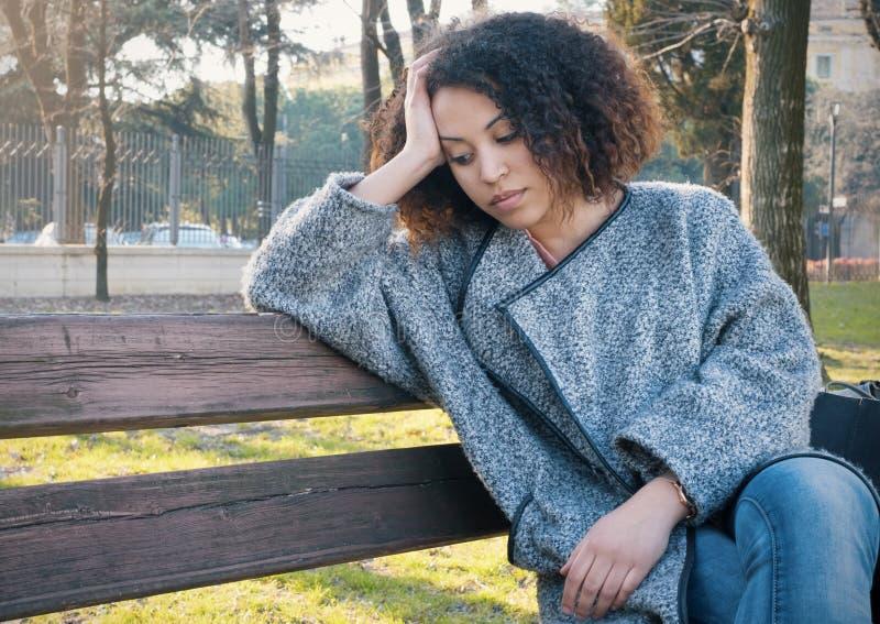 Donna di colore triste messa da solo su un banco fotografia stock