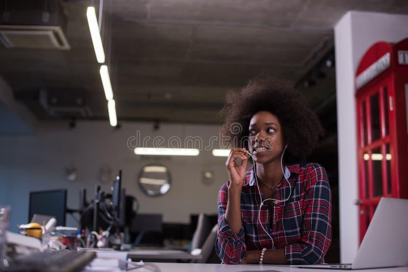 Donna di colore in ufficio moderno che speeking sul telefono sopra le cuffie fotografia stock