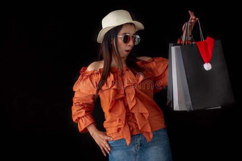 Donna di compera asiatica sorpresa con il sacchetto della spesa di Black Friday ed il cappello di Santa Claus dentro su fondo ner fotografia stock