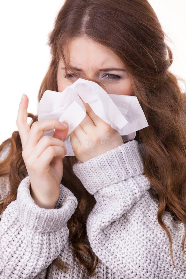 Donna di congelamento malata che starnutisce nel tessuto immagini stock