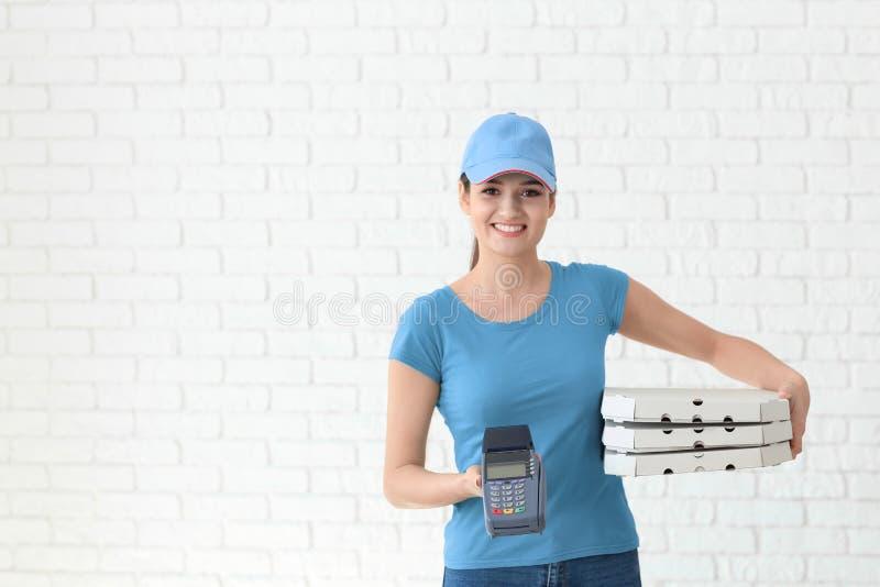 Donna di consegna con i contenitori di pizza del cartone ed il terminale di pagamento sul fondo del muro di mattoni immagini stock libere da diritti