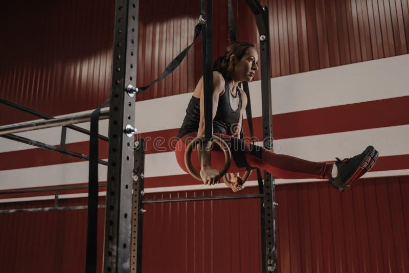 Donna di Crossfit che fa gli esercizi dell'ABS sugli anelli relativi alla ginnastica alla palestra fotografia stock libera da diritti