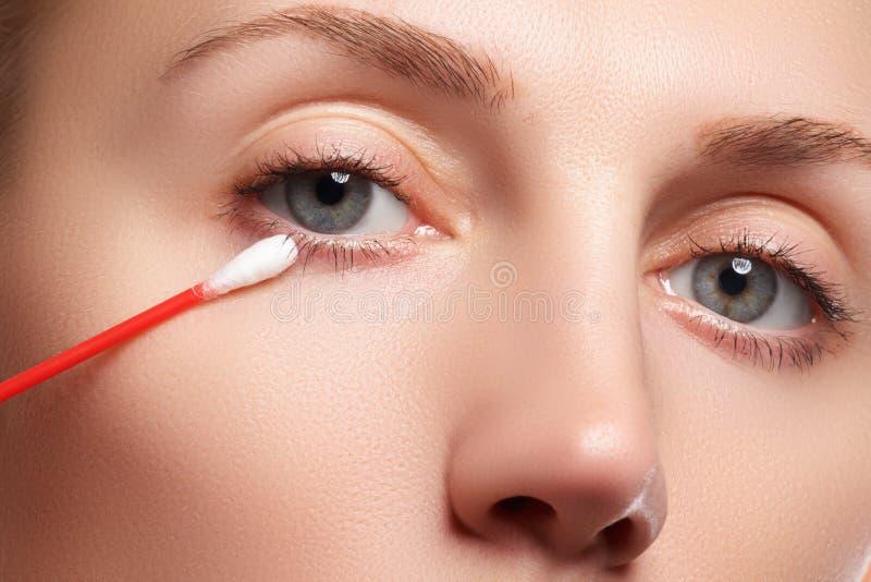 Donna di cura di pelle che rimuove trucco del fronte con il tampone di cotone Concetto di cura di pelle Modello caucasico con pel fotografia stock