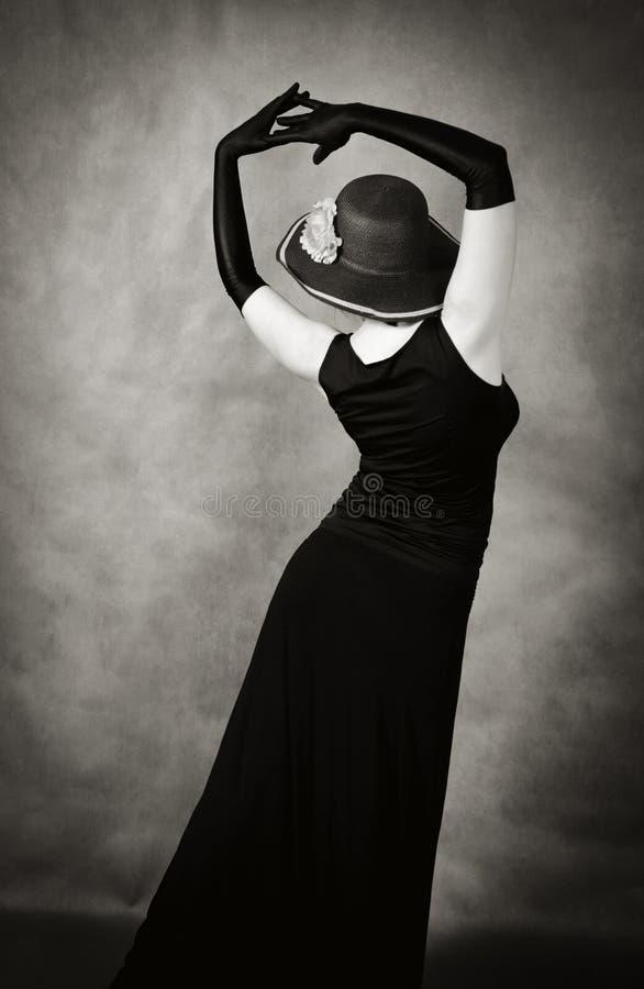 Donna di dancing in un cappello e nei guanti lunghi immagine stock