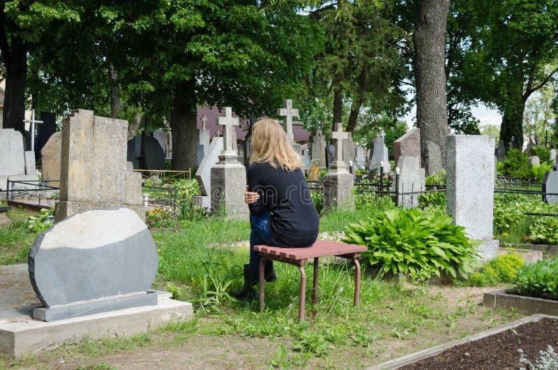 Donna di dispiacere shrinked vicino alla tomba del marito del padre fotografia stock libera da diritti