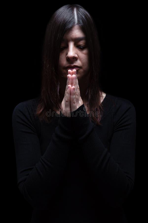 Donna di dolore che prega, con le mani piegate nel culto al dio fotografia stock libera da diritti