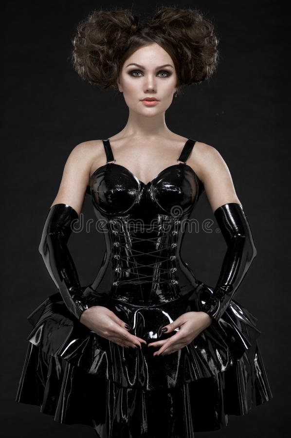 Donna di Exy castana nel vestito e nelle catene dal lattice del feticcio fotografia stock libera da diritti