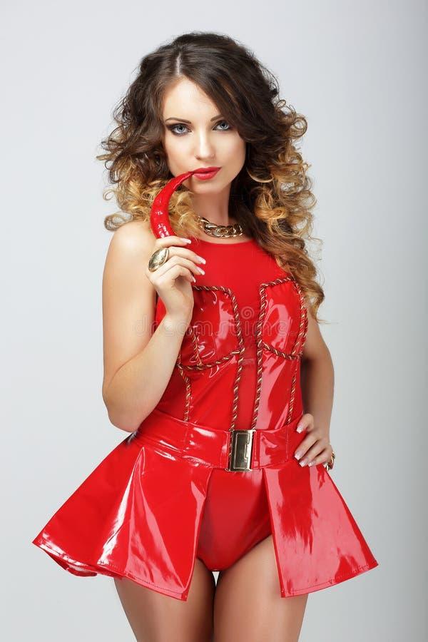 Donna di fascino in attrezzatura di gomma rossa che morde Chili Pepper immagine stock libera da diritti