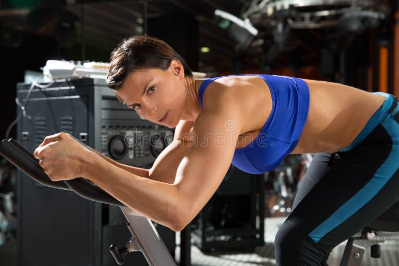 Donna di filatura dell'istruttore del monitor di aerobica alla palestra immagine stock