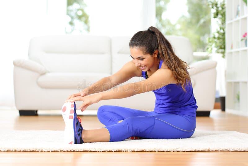 Donna di forma fisica che allunga le gambe a casa fotografie stock