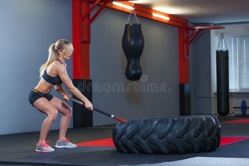 Donna di forma fisica che colpisce la gomma della ruota con la slitta del martello nella palestra fotografie stock
