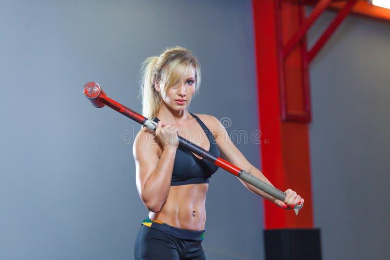 Donna di forma fisica che colpisce la gomma della ruota con la slitta del martello nella palestra immagine stock libera da diritti