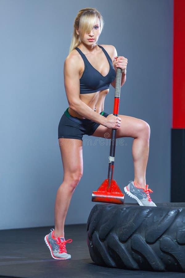 Donna di forma fisica che colpisce la gomma della ruota con la slitta del martello nella palestra fotografia stock