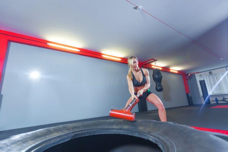 Donna di forma fisica che colpisce la gomma della ruota con la slitta del martello nella palestra immagini stock libere da diritti