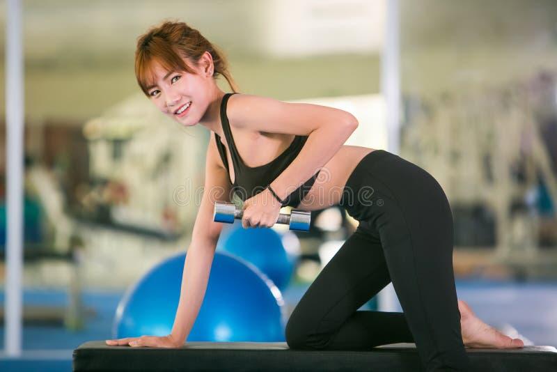 Donna di forma fisica che fa gli allenamenti del bicipite con le teste di legno in una palestra immagini stock