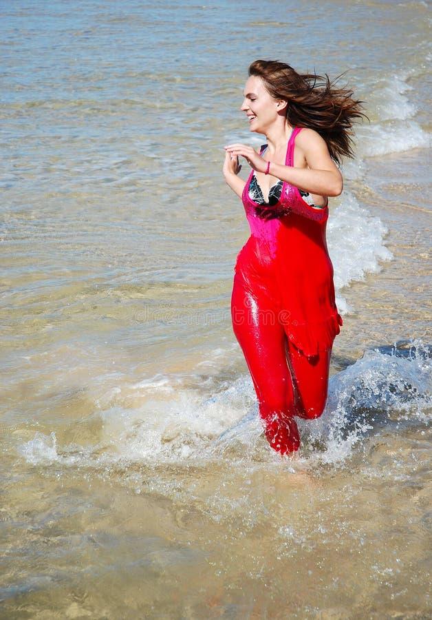 Donna di forma fisica che funziona nel mare fotografia stock