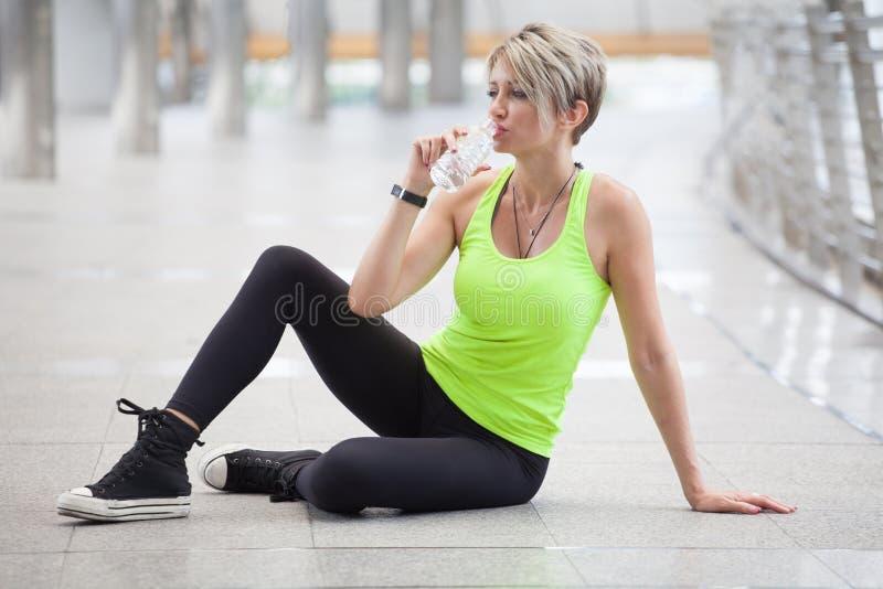 donna di forma fisica che prende una rottura dopo l'allenamento che esercita bere con una bottiglia di acqua sulla via in città u fotografie stock libere da diritti