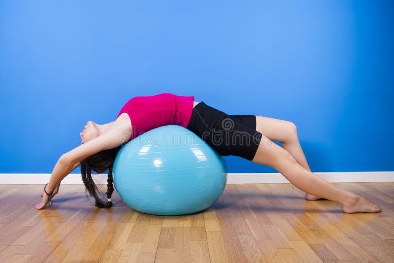 Donna di forma fisica che si esercita con la palla all'interno. immagine stock