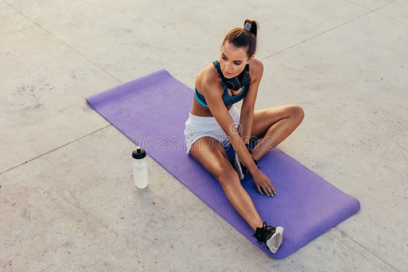 Donna di forma fisica che si rilassa dopo l'allenamento all'aperto fotografia stock libera da diritti