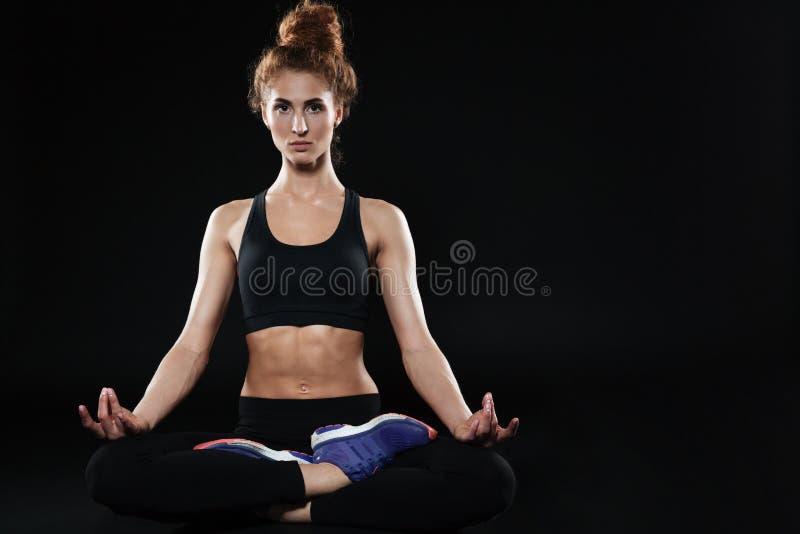 Donna di forma fisica che si siede nella posa e nel meditare del loto fotografie stock