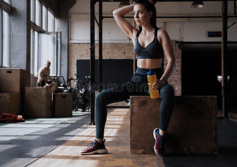 Donna di forma fisica che si siede su una scatola alla palestra dopo il suo allenamento immagine stock libera da diritti