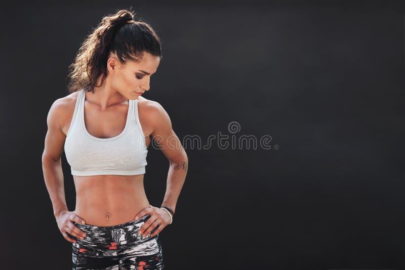 Donna di forma fisica che sta con le sue mani sulle anche immagine stock