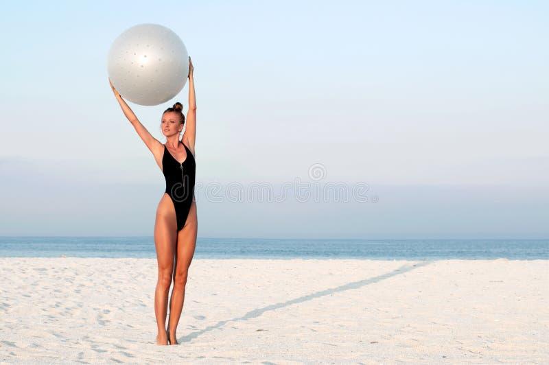 Donna di forma fisica con la palla di misura sulla spiaggia all'aperto immagini stock