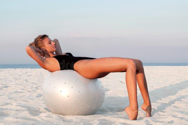 Donna di forma fisica con la palla di misura sulla spiaggia all'aperto fotografia stock libera da diritti