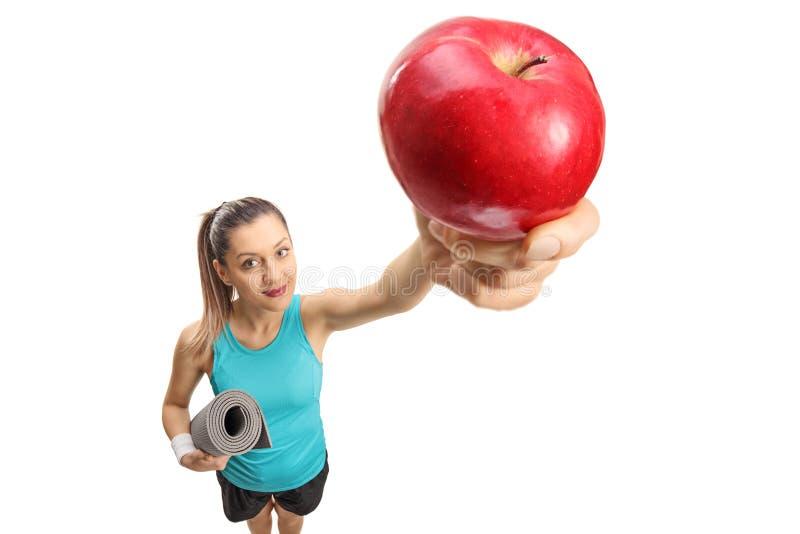 Donna di forma fisica con una stuoia di esercizio e una mela fotografie stock