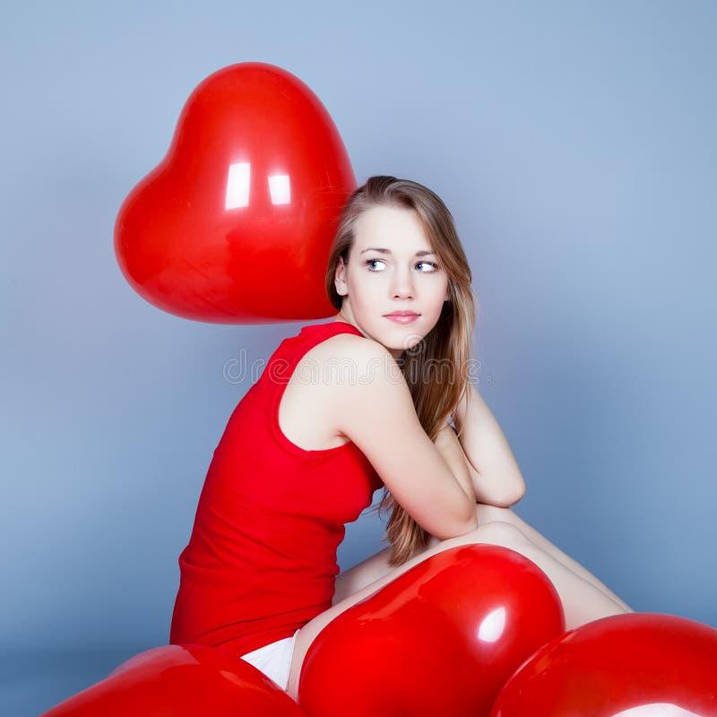Donna di giorno dei biglietti di S. Valentino che tiene cuore rosso fotografia stock libera da diritti
