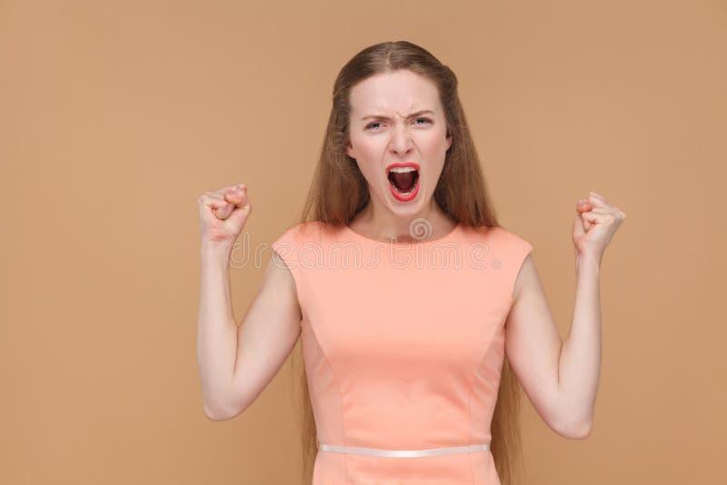 Donna di grido aggressiva che esamina macchina fotografica fotografia stock