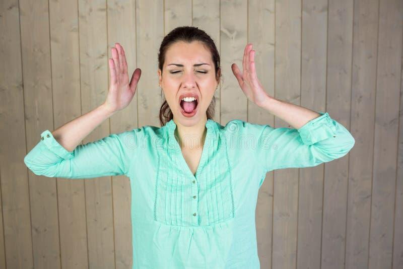 Donna di grido che gesturing con gli occhi chiusi fotografia stock libera da diritti