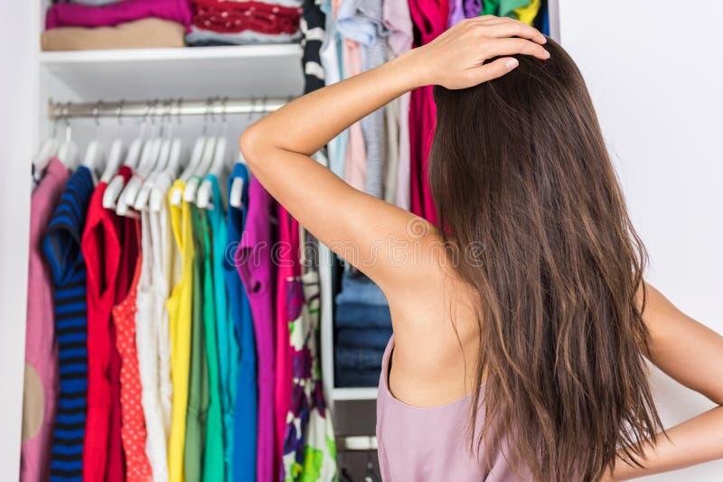 Donna di indecisione che sceglie attrezzatura nel gabinetto di vestiti fotografie stock libere da diritti