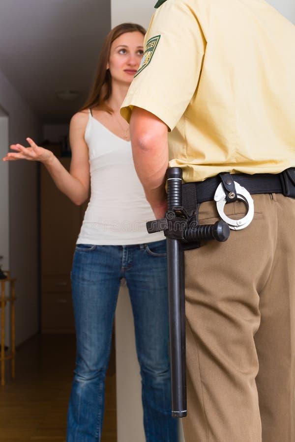 Donna di interrogazione dell'ufficiale di polizia all'entrata principale immagine stock libera da diritti