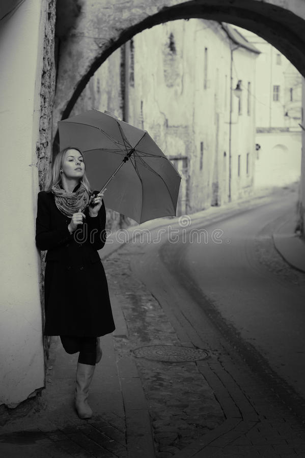 Donna di Lonelly con l'ombrello in una via, retro immagini stock libere da diritti