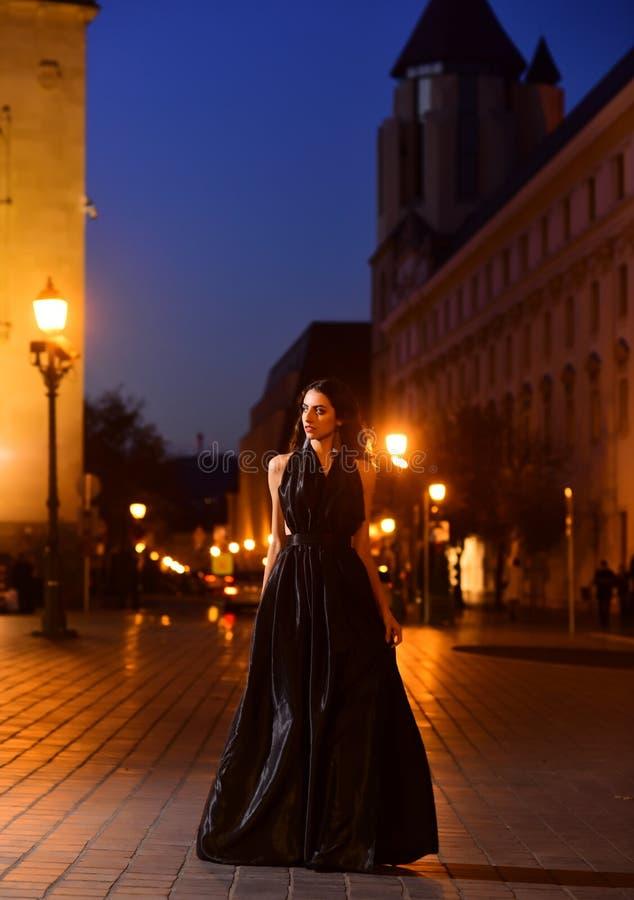 Donna di lusso in vestito da sera alla città di notte che va alla ragazza sexy del partito di promenade in vestito elegante Modo  immagini stock libere da diritti