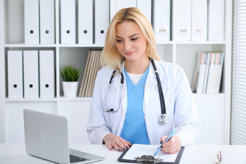 Donna di medico sul lavoro Ritratto del medico biondo sorridente allegro che per mezzo del computer della compressa mentre sedend fotografia stock libera da diritti