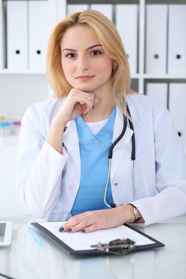Donna di medico sul lavoro Ritratto del medico biondo sorridente allegro che si siede allo scrittorio Concetto di sanità e della  fotografia stock libera da diritti