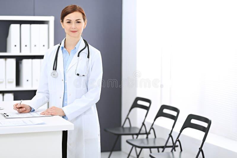 Donna di medico sul lavoro Ritratto del medico femminile che riempie forma medica mentre stando reception vicina alla clinica immagini stock