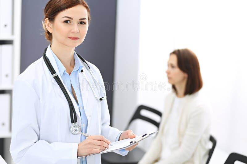 Donna di medico sul lavoro Ritratto del medico femminile che riempie forma medica mentre stando reception vicina alla clinica immagini stock libere da diritti