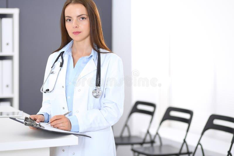 Donna di medico sul lavoro Ritratto del medico femminile che sta reception vicina alla clinica o all'ospedale di emergenza fotografia stock libera da diritti