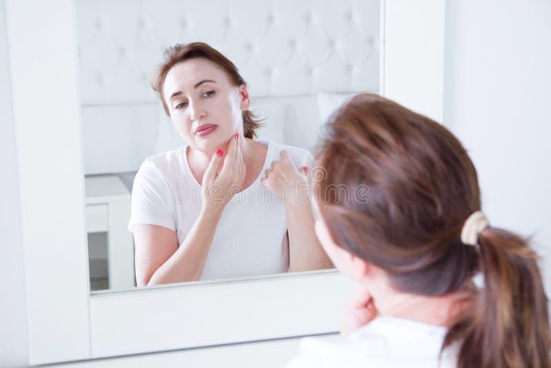 Donna di medio evo che guarda in specchio sul fronte Grinze e concetto antinvecchiamento di cura di pelle Fuoco selettivo fotografia stock
