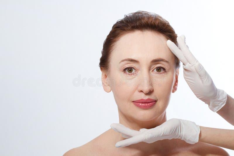 Donna di medio evo che ottiene trattamento della stazione termale Massaggio di fronte Botox e collagene antinvecchiamento Il conc fotografie stock
