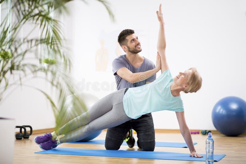 Donna di medio evo che si esercita sulla stuoia blu durante la fisioterapia con giovane medico maschio fotografie stock libere da diritti