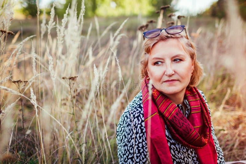 Donna di mezza età alla moda che raffredda nel campo di autunno Vestiti d'uso ed accessori di signora senior Armonia ed equilibri fotografia stock libera da diritti