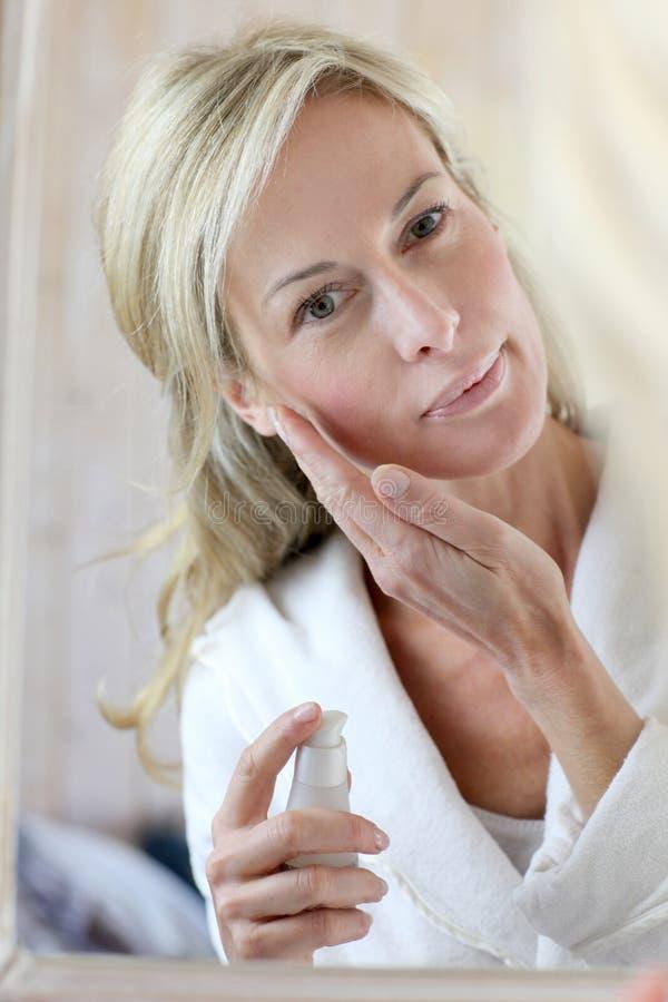 Donna di mezza età attraente che applica i cosmetici immagini stock