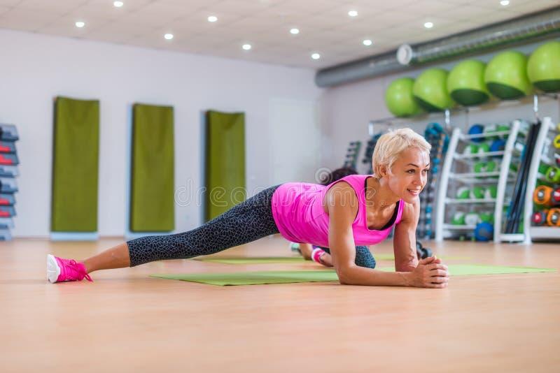 Donna di mezza età bionda esile attraente che fa tavolato o che allunga esercizio sulla stuoia contro l'attrezzatura di sport var immagini stock