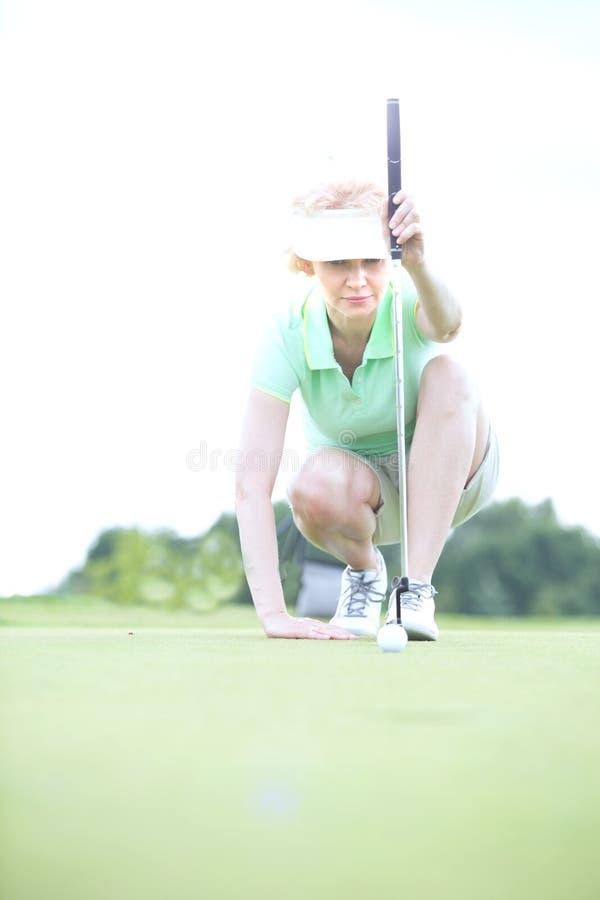 Donna di mezza età che tende palla al campo da golf fotografia stock